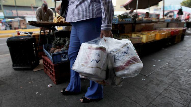 In Caracas verlässt eine Frau einen Laden, in dem sie Toilettenpapier gekauft hat.