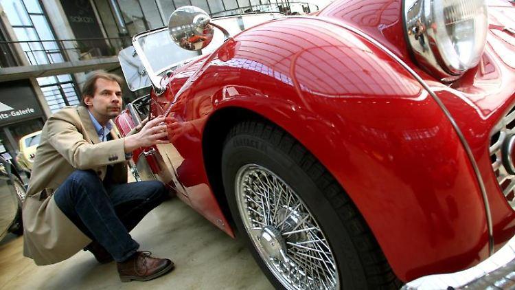 Frank Wilke schätzt einen Triumph TR 3a Roadster von 1960 an. Er weiß, dass Oldtimer immer öfter auch als Geldanlage gekauft werden. Foto: Roland Weihrauch