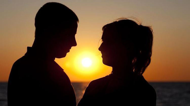 Ein Paar steht bei Sonnenuntergang am Ostseestrand von Warnemünde.jpg