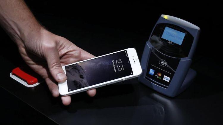 So funktioniert das mobile Bezahlen: Das Telefon wird an das Lesegerät an der Kasse gehalten und die Zahlung per Fingerabdruck auf dem iPhone-Sensor bestätigt. Foto: Monica Davey