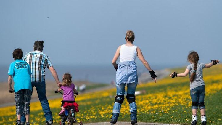 Eine Familie ist mit Inline-Skates, Fahrrad und Tretroller unterwegs. Foto: Matthias Balk