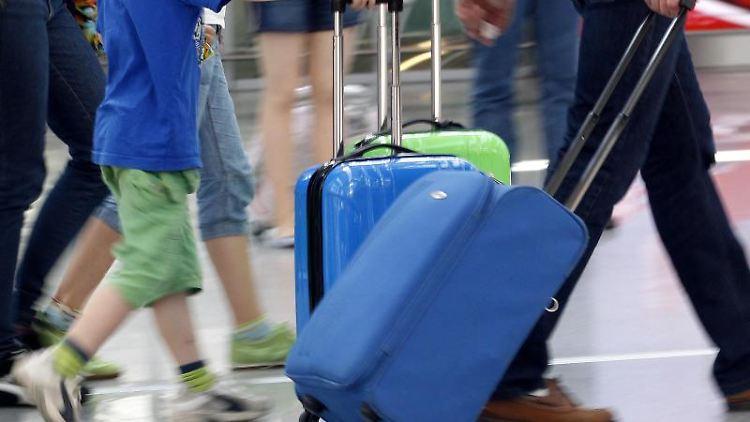 Reisende mit Koffern auf einem Flughafen