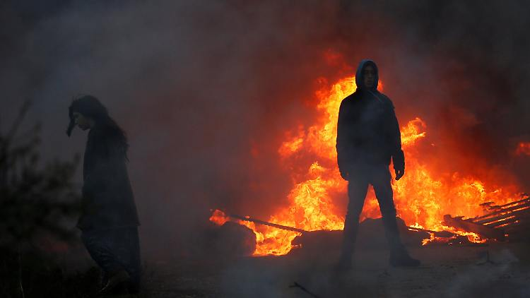 Protesters stand next to fire at the entrance to the Israeli settler outpost of Amona in the occupied West Bank early morning February 1, 2017.  REUTERS/Ronen Zvulun