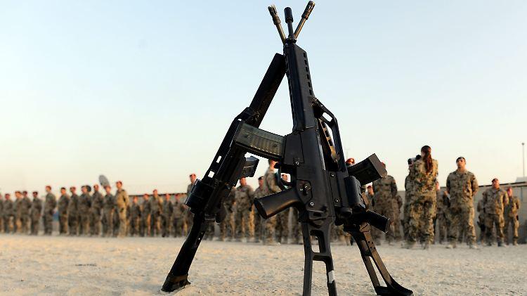 ARCHIV - Gewehre vom Typ G36 stehen am 17.08.2011 in Kundus in Afghanistan vor einer Gruppe von Bundeswehrsoldaten.