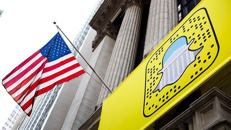 ARCHIV -Das Snapchat-Logo hängt am 17.11.2016 unter einer US-Flagge an der Außenfassade der New York Stock Exchange in New York, in New York. Die Macher der populären Foto-App Snapchat hatten laut Medienberichten zu diesem Zeitpunkt bereits den mit Spannung erwarteten Börsengang auf den Weg gebracht. (zu dpa