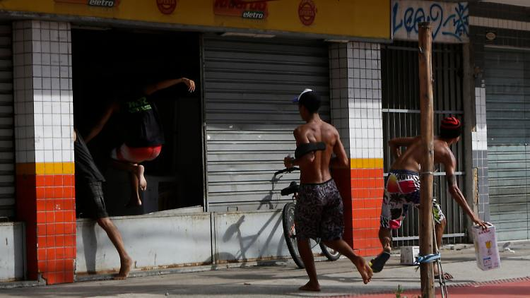 Looters plunder an electronic store, in Vitoria, Espirito Santo state, Brazil, Monday, Feb 6, 2017. Protests by the friends and family of military police in Espirito Santo have led to an increase in crime and forced the shut-down of some state services, authorities said Monday. (AP Photo/Diego Herculano)
