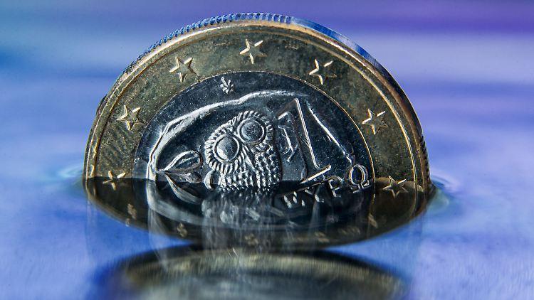 ARCHIV - ILLUSTRATION - Eine griechische Euro-Münze steht am 22.06.2015 in Schwerin (Mecklenburg-Vorpommern) in einer Wasserfläche, in der sich die griechische Flagge spiegelt (gestelltes Foto). (zu dpa