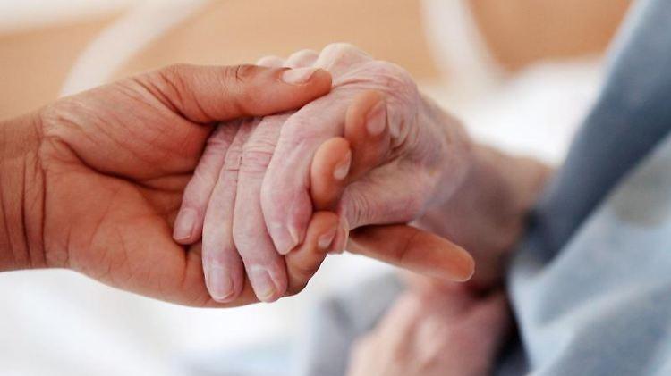 Eine Pflegerin hält die Hand einer Bewohnerin einer Altenheims. Foto: Oliver Berg/Archiv