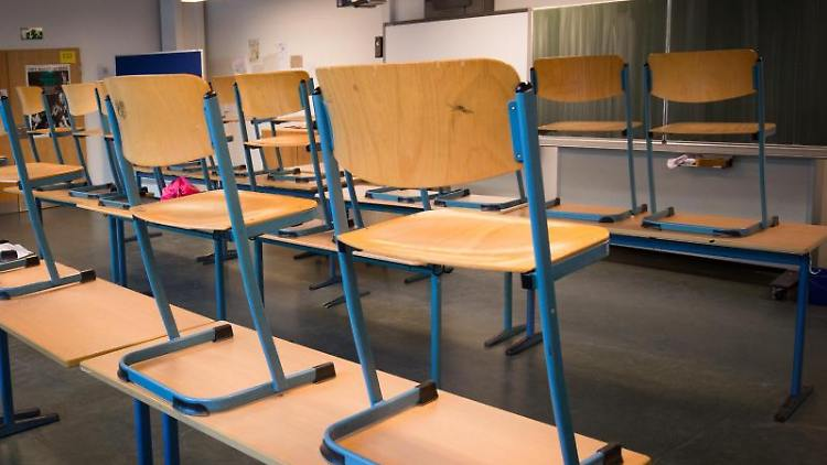 Stühle stehen auf den Tischen in einem Klassenzimmer eines Gymnasiums. Foto: Christian Charisius/Archiv
