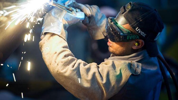 Ein Mann aus Somalia, der zuvor als Schweißer ausgebildet wurde, arbeitet an einem Stahlsegment. Foto: Patrick Pleul/Archiv