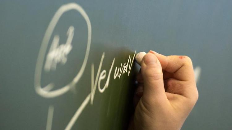 Eine Schülerin fügt an ein Wort an der Tafel einen Hinweis an. Foto: Andreas Arnold/Archiv