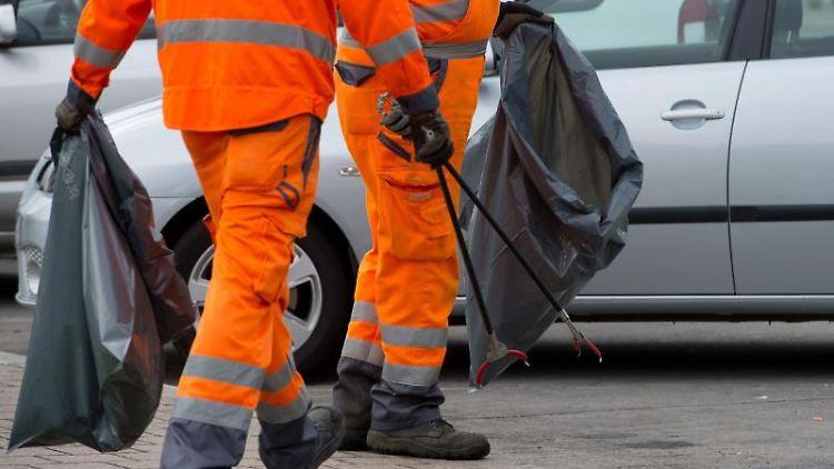Mitarbeiter der Autobahnmeisterei sammeln an der Autobahnraststätte mit einer Greifzange Müll. Foto: Sebastian Kahnert/Archiv
