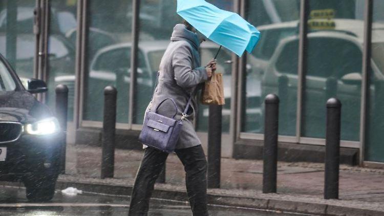 Eine Passantin geht in der Innenstadt beiWind und Regen über eine Kreuzung. Foto: Frank Rumpenhorst/Archiv