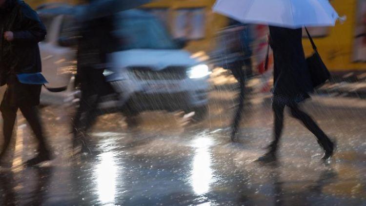 Passanten mit Regenschirmen gehen während eines Gewitters über die Straße. Foto: Monika Skolimowska/Archiv