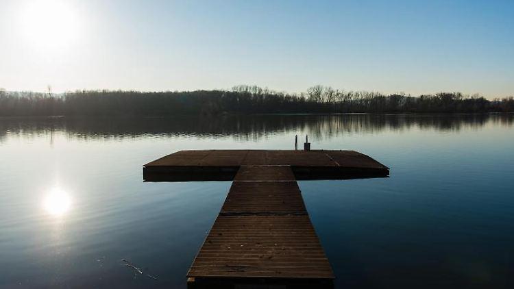 Ein Steg liegt bei strahlend blauem Himmel auf dem Wasser des Baggersees. Foto: Nicolas Armer/Archiv