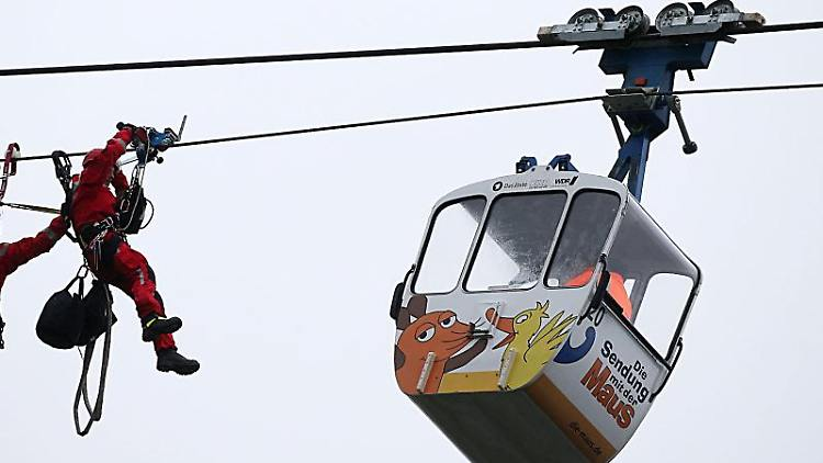 Höhenretter der Feuerwehr nähern sich einer Gondel der Kölner Seilbahn. Foto: Oliver Berg