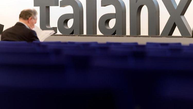 Ein Aktionär liest bei der Hauptversammlung der Talanx AG im Hannover Congress Centrum in einer Zeitung. Foto: Sebastian Gollnow/Archiv