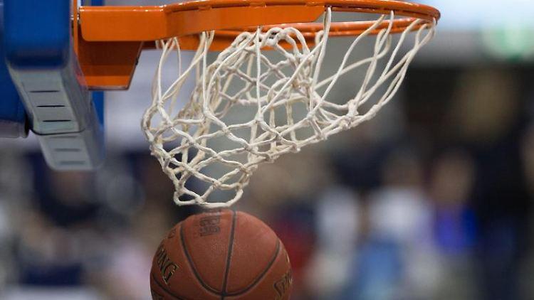 Ein Basketball fällt durch das Netz vom Basketballkorb. Foto: Lukas Schulze/Archiv