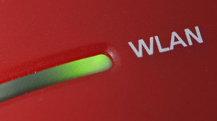 Eine Lampe leuchtet an einem WLAN-Router. Foto: Armin Weigel/Archiv