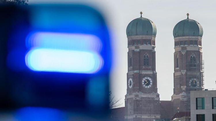 Ein Blaulicht einer Polizeistreife ist vor den Türmen der Frauenkirche in München zu sehen. Foto: Lino Mirgeler/Archiv