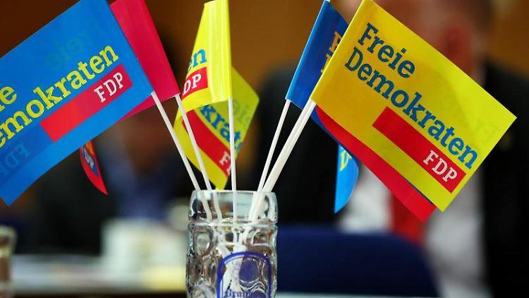 Fähnchen der FDP stehen während eines Landesparteitags in Bayern auf einem Tisch. Foto: Daniel Karmann/Archiv