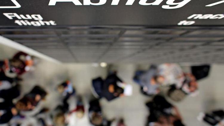 Flugreisende warten in einer Schlange vor der Sicherheitskontrolle auf dem Flughafen. Foto: Jan Woitas/Archiv