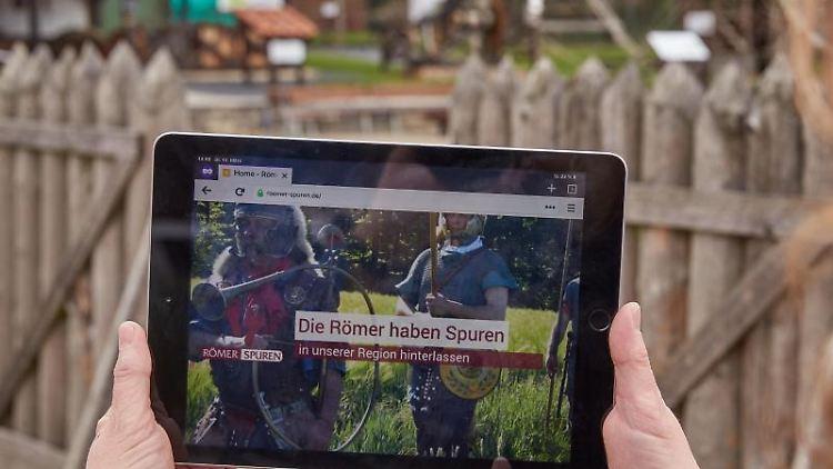 Eine betrachtet auf ihrem Tablet-Computer das neue Internetportal