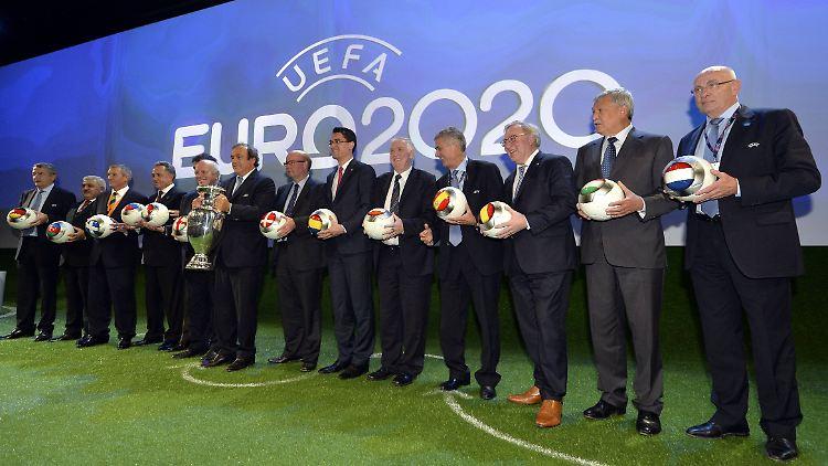 Michel Platini (mit Pokal) inmitten von Vertretern der Gastgebernationen.