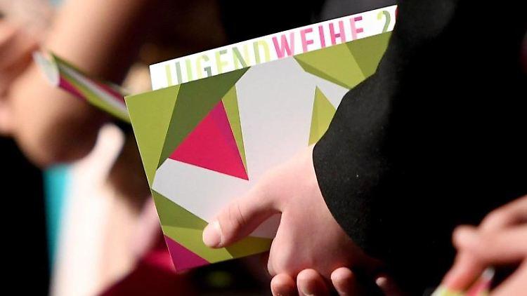 Jugendliche erhalten ihre Urkunde bei der Jugendweihe. Foto: Britta Pedersen/Archivbild