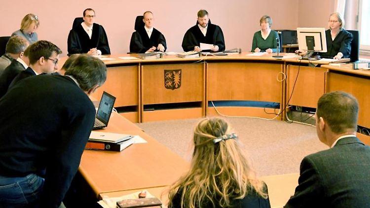 Zwei der Angeklagten (l. vorn bzw. l. hinten, graue Jacke und vorn r.), Anwälte und Richter sitzen im Gerichtssaal. Foto: Carsten Rehder