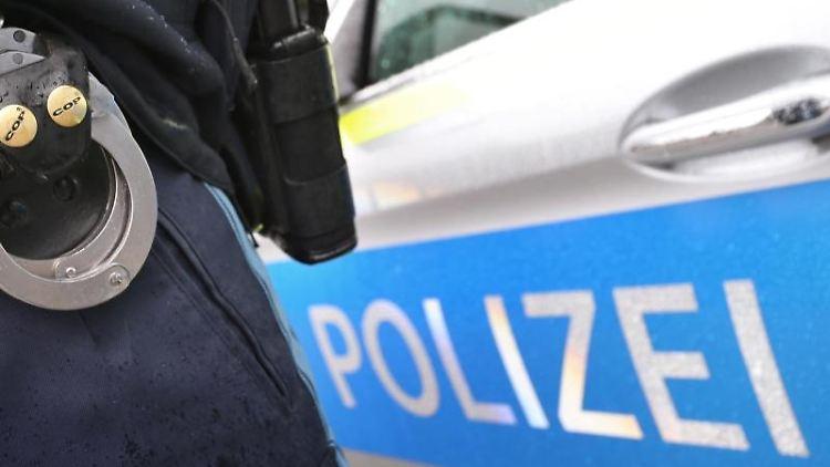 Ein Polizist mit Handschellen und einer Pistole am Gürtel steht vor einem Streifenwagen. Foto: Karl-Josef Hildenbrand/Archiv