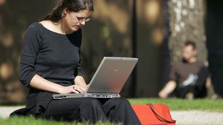 Eine Studentin sitzt in Potsdam mit einem Latop auf einer Wiese auf dem Campus des Hasso-Plattner-Instituts. Foto: Michael/Archivbild