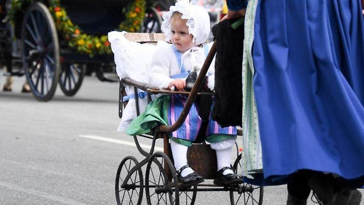 Ein Kind im historischen Outfit und einem ebensolchen Kinderwagen wird geschoben. Foto: Tobias Hase/Archiv