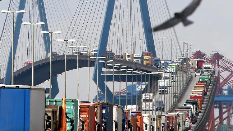 Mit Containern beladene Lastwagen stauen sich auf der Köhlbrandbrücke im Hafen von Hamburg. Foto: Christian Charisius/Archivbild