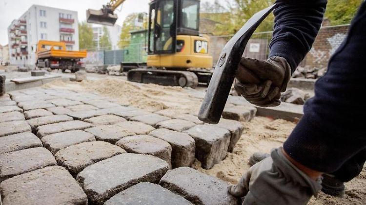 Ein Bauarbeiter setzt Pflastersteine. Foto: Christoph Soeder/Archivbild