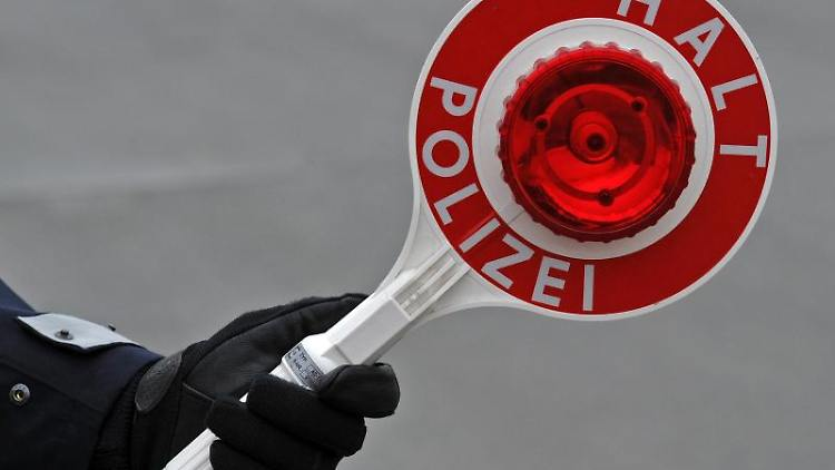 Ein Polizist hält eine Kelle