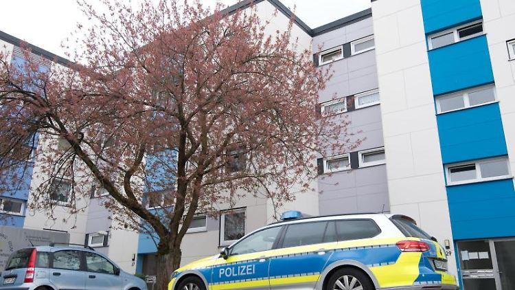 Ein Polizeifahrzeug steht vor einem Mehrfamilienhaus in Salzgitter. Foto: Julian Stratenschulte