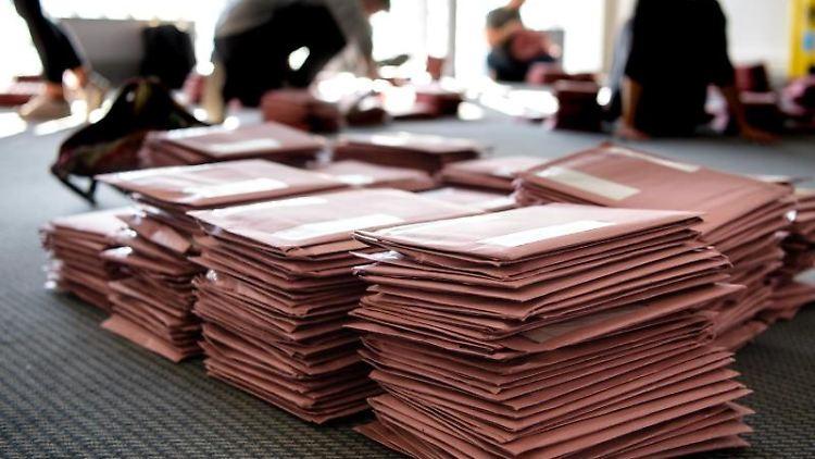 Wahlhelfer sortieren in einem Briefwahlzentrum Briefumschläge. Foto: Matthias Balk/Archivbild