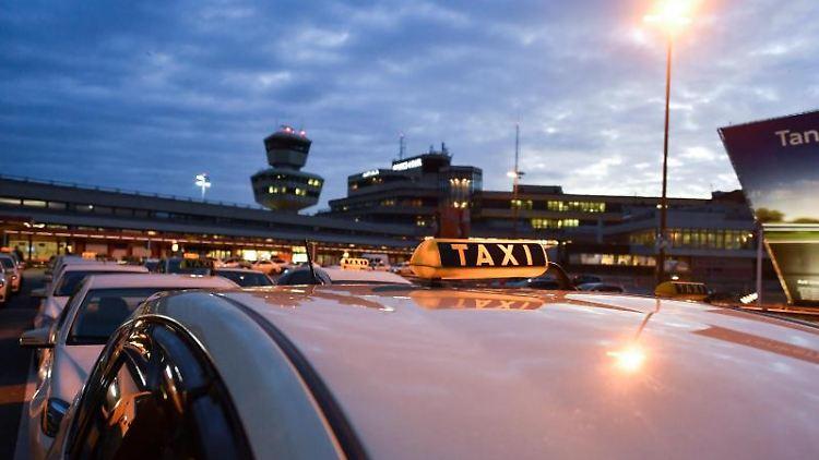 Taxis stehen am frühen Morgen am Flughafen Berlin-Tegel. Foto: Jens Kalaene/Archivbild