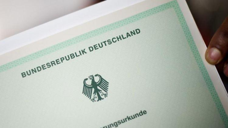 EinMann hält eine Einbürgerungsurkunde in der Hand. Foto: Julian Stratenschulte/Archivbild