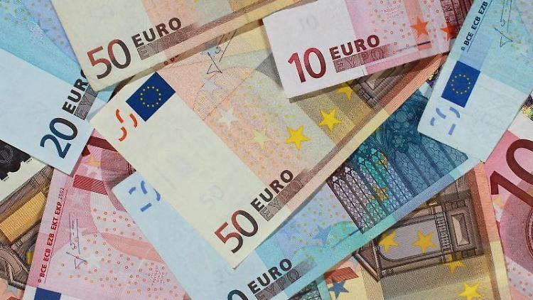 Banknoten von 50, 20 und 10 Euro liegen auf einem Tisch. Foto: Jens Wolf/Archiv