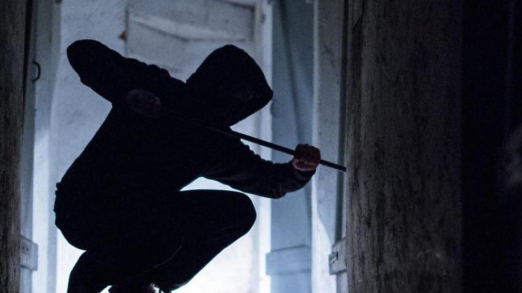Ein fiktiver Einbrecher hebelt mit einem Brecheisen eine Tür auf (gestellte Szene). Foto: Silas Stein/Archiv