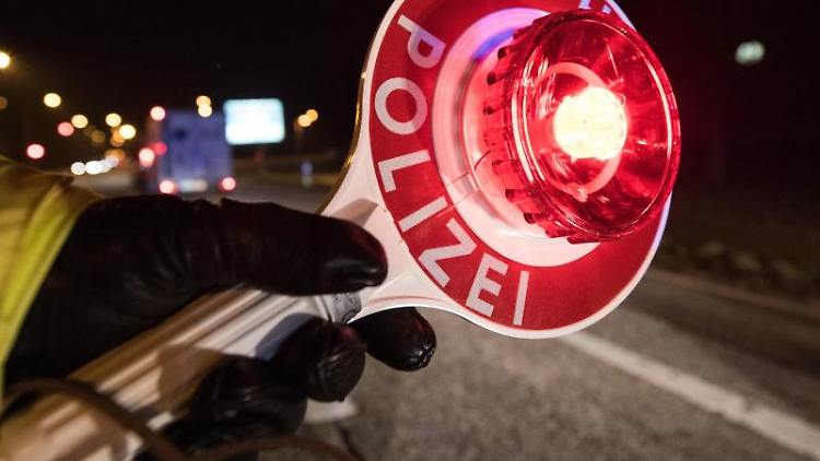 Ein Polizist hält während einer Verkehrskontrolle mit einer Haltekelle Fahrzeuge an. Foto: Patrick Seeger/Archiv