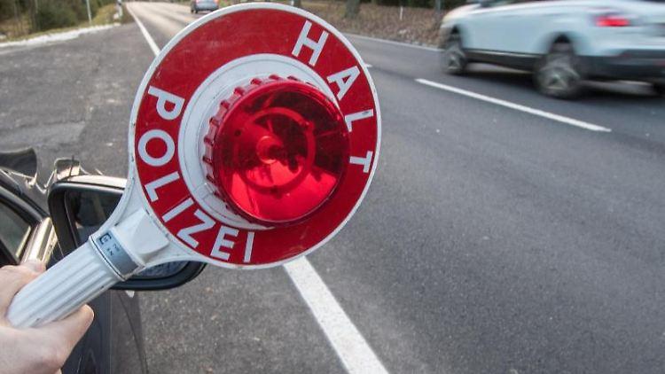 Ein Polizist hält eine Polizeikelle. Foto: Armin Weigel/Archiv