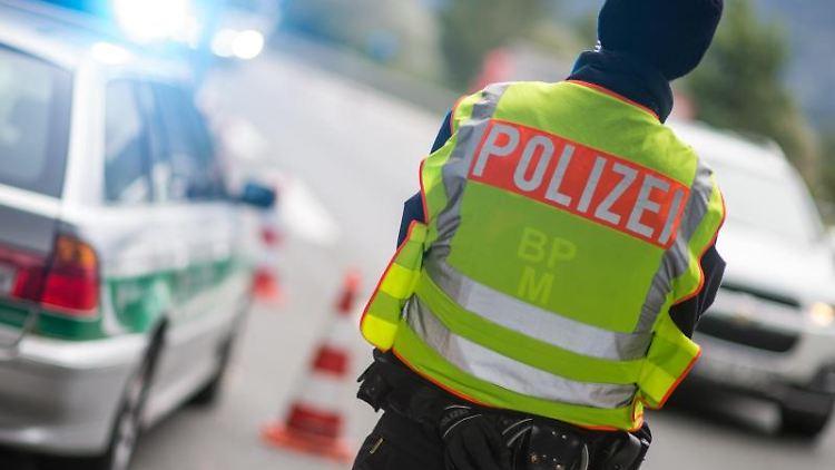 Ein Polizeibeamter beobachtet an einer Grenzkontrolle Fahrzeuge, die von Österreich nach Deutschland kommen. Foto: Matthias Balk/Archivbild