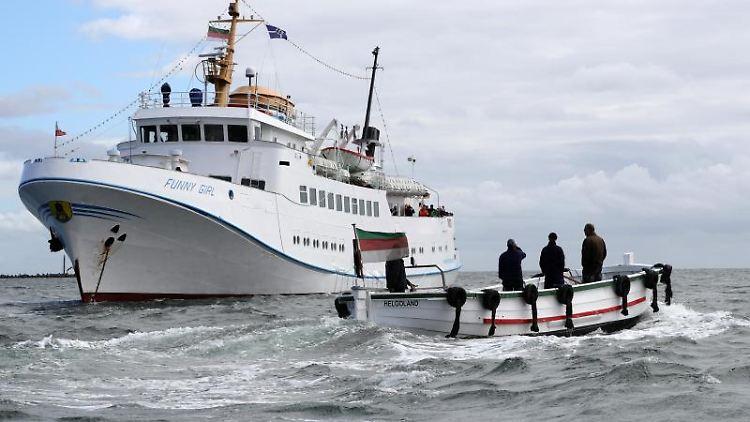 Ein Börteboot ist auf dem Weg zu dem Ausflugsschiff Funny Girl. Foto:Christian Charisius/Archivbild