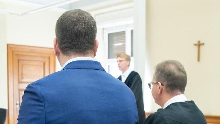 Ein wegen Störung der Totenruhe angeklagter Bestatter (l) steht mit seinem Anwalt Ulrich Spieß in einem Sitzungssaal. Foto:DanielKarmann