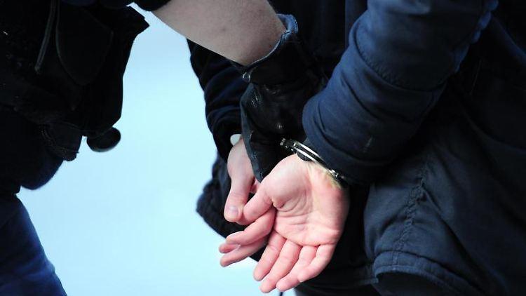Ein Polizist führt einen mit Handschellen gefesselten Mann ab. Foto: Daniel Reinhardt/Archivbild