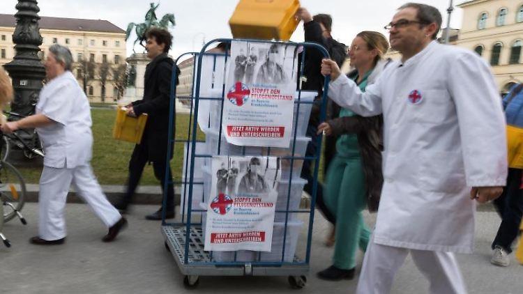 Organisatoren des Volksbegehren Pflegenotstand gehen mit gesammelten Unterschriften zum Innenministeriumn. Foto: Peter Kneffel/Archivbild