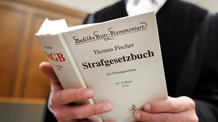 Ein Richter hält das Strafgesetzbuch (StGB) in der Hand. Foto: Oliver Berg/Archivbild